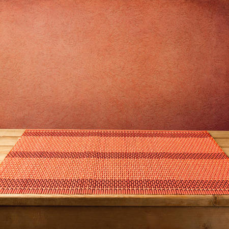 tablecloth: Bamboo tablecloth on wooden table over grunge red background