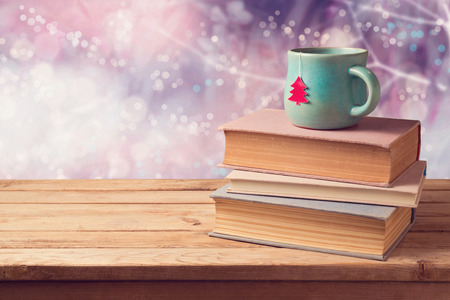 blue christmas lights: Christmas cup of tea and vintage books on wooden table over beautiful winter bokeh background with copy space