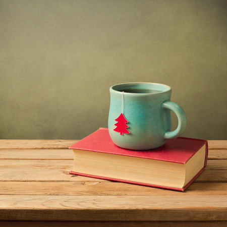 Christmas tea cup and book on wooden table Stock Photo