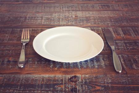Assiette vide avec un couteau et une fourchette sur la table en bois millésime Banque d'images - 40987306