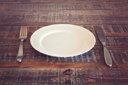 Empty plate with knife and fork on vintage wooden table Stock Photo