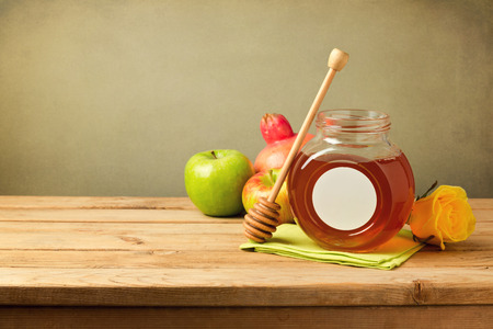 Honey and apples on wooden table