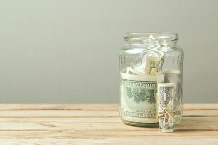 factura: Dinero en tarro de cristal en la mesa de madera