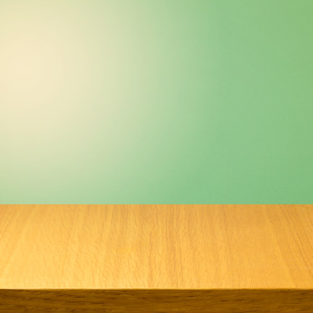 solid color: Empty wooden modern table over green solid color background Stock Photo