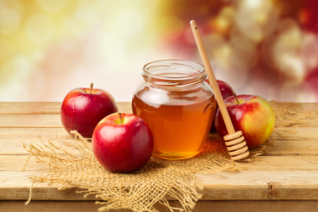 Apples with honey jar on wooden table over bokeh background Stockfoto