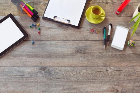 オフィスの机は、タブレット、スマート フォン、コーヒーのカップを持つテンプレートを模擬します。コピー スペースを上から表示します。