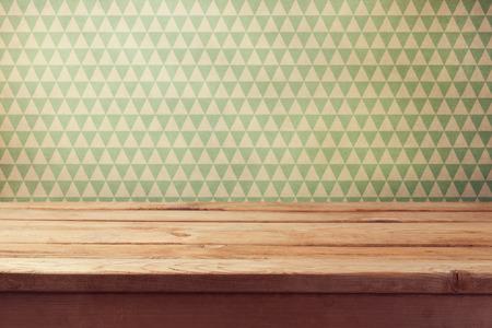 Uitstekende achtergrond met lege houten tafel over behang Stockfoto