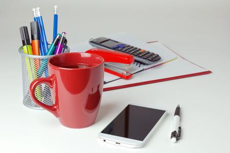 articulos de oficina: Teléfono y artículos de oficina móvil sobre mesa blanca. Concepto de negocio