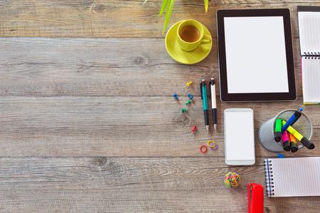 タブレット、スマート フォンのコーヒー カップとオフィス デスク背景。コピー スペースを上から表示します。