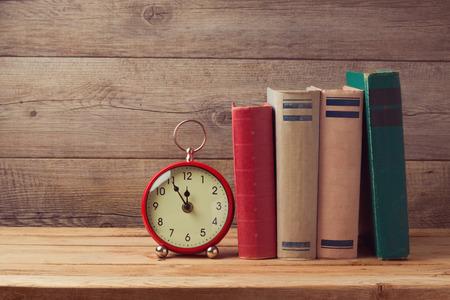 ヴィンテージ本や木製のテーブルの時計 写真素材