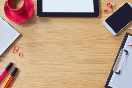 テーブル、スマート電話、メモ帳、コーヒー カップを持つ近代的なオフィス テーブル背景。コピー スペースを上から表示します。