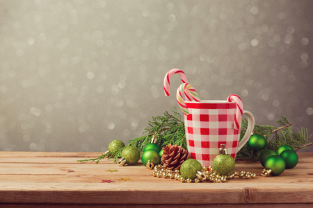 christmas baubles: Christmas holiday decorations with checked cup and candy on wooden table Stock Photo
