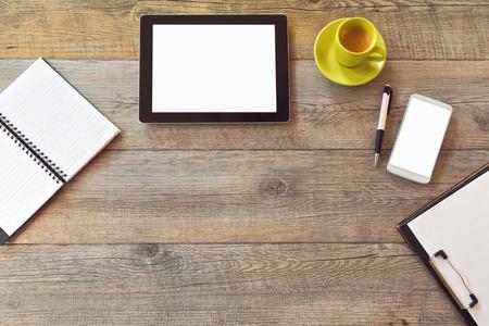 タブレット、スマート フォン、ノートブック、コーヒーのカップを持つテンプレートをモックのオフィスの机。コピー スペースを上から表示します