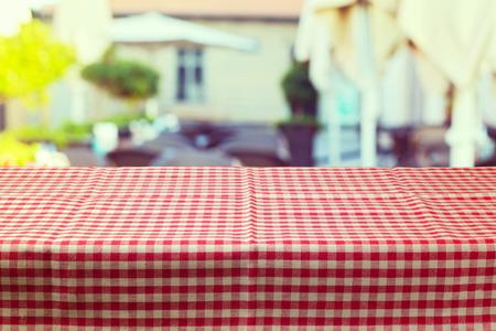 Tavolo con tovaglia rossa controllata su sfocatura ristorante sfondo Archivio Fotografico