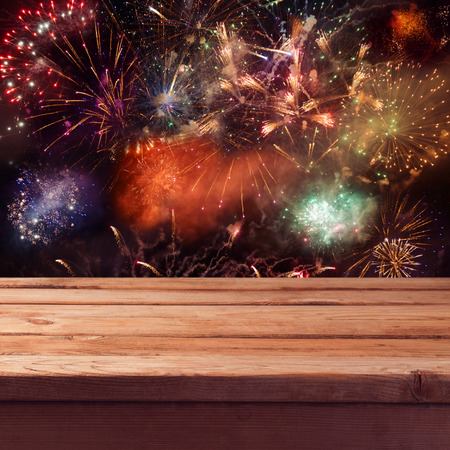 firework display: Empty wooden deck table over fireworks background