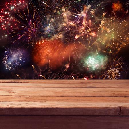 fuegos artificiales: Vaciar mesa de terraza de madera sobre fondo de fuegos artificiales