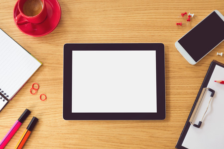overhead: Tablet with blank white screen on wooden table. Office desk mock up. View from above Stock Photo
