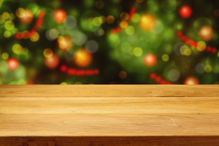 holiday display: Empty wooden deck table over Christmas tree bokeh background