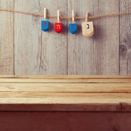 string top: Empty wooden deck table with Hanukkah dreidel spinning top hanging on string Stock Photo