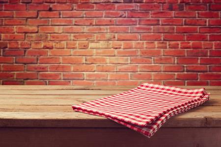 レンガの壁にテーブル クロスをかけた木製のテーブル 写真素材