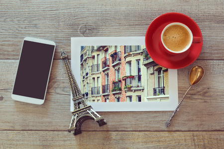 Photo of buildings in Paris on wooden table with coffee cup and smart phone. View from above