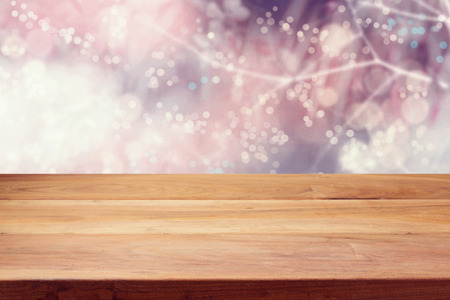 christmas lights display: Empty wooden deck table over winter bokeh background