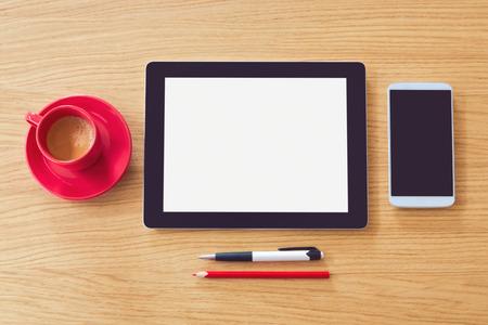 木製のテーブルで空白のスクリーンを搭載したタブレットします。モックアップのオフィスの机。上からの眺め