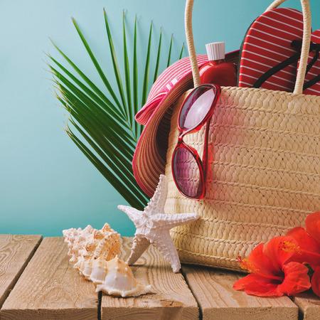 Borsa Vacanze estive con articoli da spiaggia sul tavolo in legno