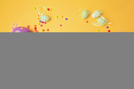 papiermache: Easter decorations on yellow background.  Papier-mache eggs painted with chalkboard paint. View from above.