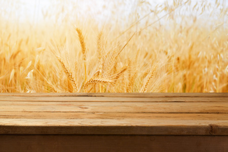 wooden desk: Empty wooden table over wheat field background Stock Photo