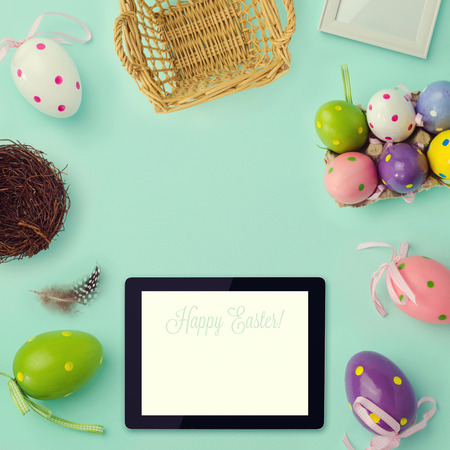 Easter holiday background with retro filter effect. Easter eggs decorations and tablet. View from above
