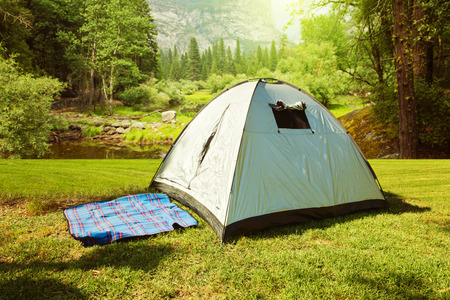 camping site: Camping tent on grass over beautiful forest Stock Photo
