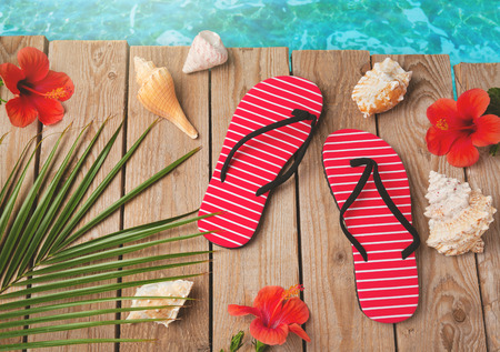 sandal tree: Flip flops and hibiscus flowers on wooden background. View from above Stock Photo