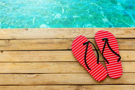 Flip flops on wooden deck over water background Stockfoto