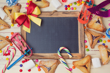 purim: Hamantaschen cookies and chalkboard on wooden white table. View from above Stock Photo