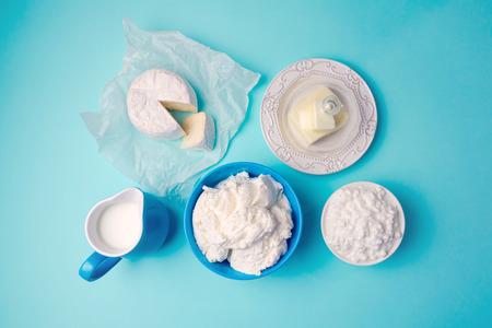 leche y derivados: La leche, el queso y la mantequilla en el fondo azul moderno. Vista desde arriba Foto de archivo