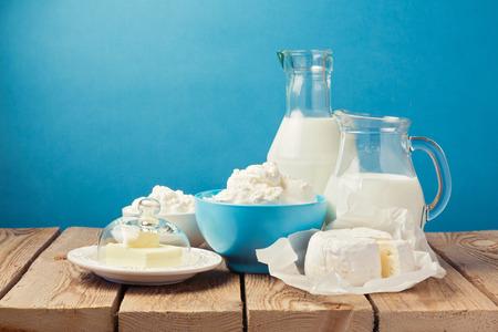 dairy: Productos lácteos en la mesa de madera sobre fondo azul