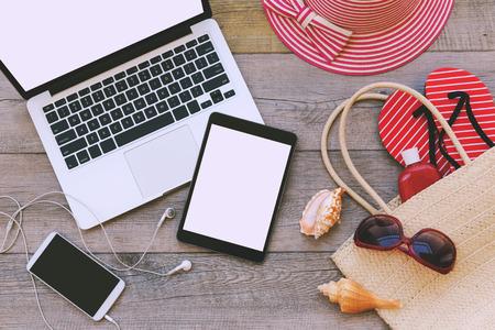 ノート パソコン、デジタル タブレット、ビーチ アイテムを木製の背景を持つスマート フォン。上からの眺め