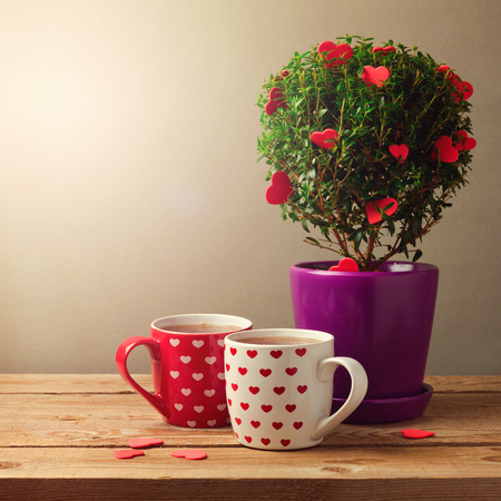 Tree plant with heart shapes and cups of tea for Valentines day celebration