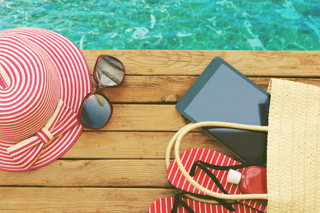 holiday summer: Summer holiday bag with tablet and flip flops on wooden deck. View from above Stock Photo