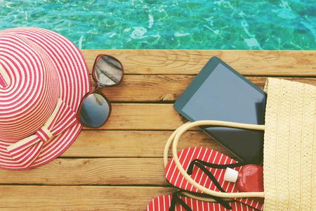 summer: Verano bolsa de vacaciones con tableta y chanclas en la cubierta de madera. Vista desde arriba