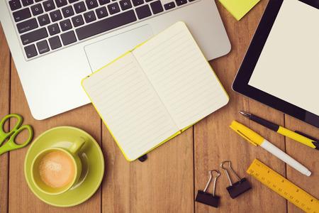 オフィスの机のモックアップのラップトップ、ノートブック、およびタブレットを持つテンプレート。上からの眺め