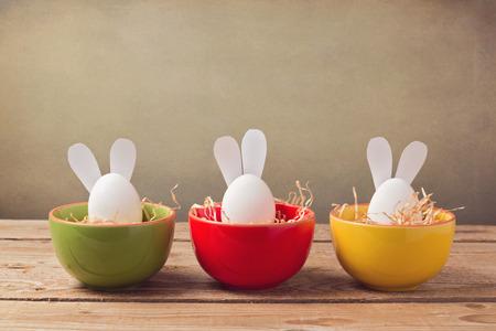 huevo: Huevos de pascua vacaciones con orejas de conejo en mesa de madera