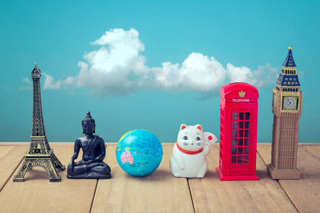 Souvenirs from around the world on wooden table over blue sky background