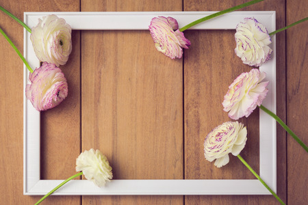 wedding border: Picture frame with flowers on wooden table. View from above