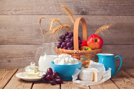 basket: Milk, cheese and fruit basket over wooden background Stock Photo