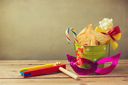 Hamantaschen cookies in bucket with grogger noise maker and carnival mask Standard-Bild