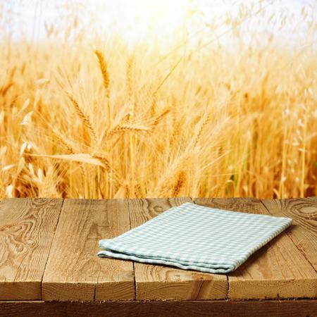 小麦フィールド背景にウッドデッキのテーブルにテーブル クロスをチェック