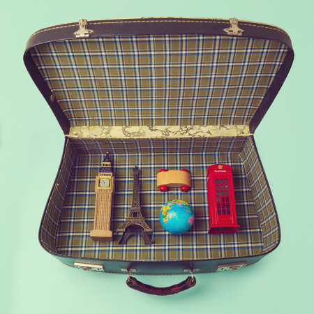suitcase packing: Summer vacation concept with suitcase and souvenirs from around the world