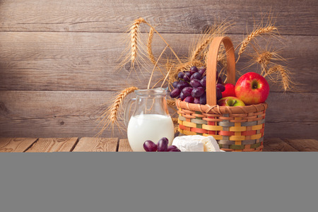 Basket with fruits and milk over wooden background
